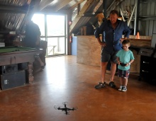 Rob showing Ayden how to pilot a drone in the barn